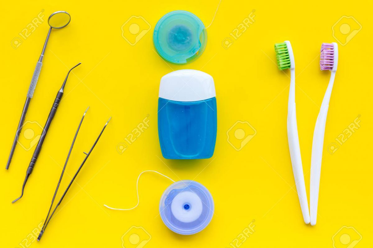 113857543-daily-oral-hygiene-for-family-toothbrush-dental-floss-and-dentist-instruments-on-yellow-background-t-1200x799.jpg